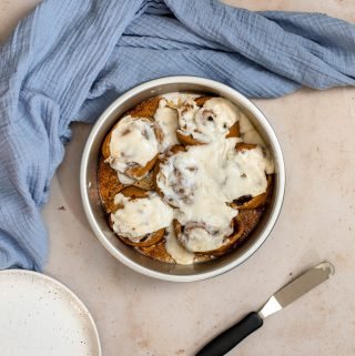 pumpkin cinnamon rolls with maple cream cheese icing in a round silver pan