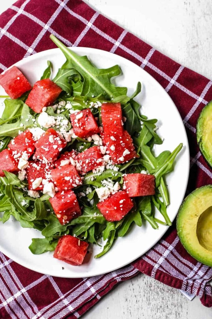 salad of watermelon, feta cheese, arugula, and avocado on a white plate on top of a red and white dishtowel