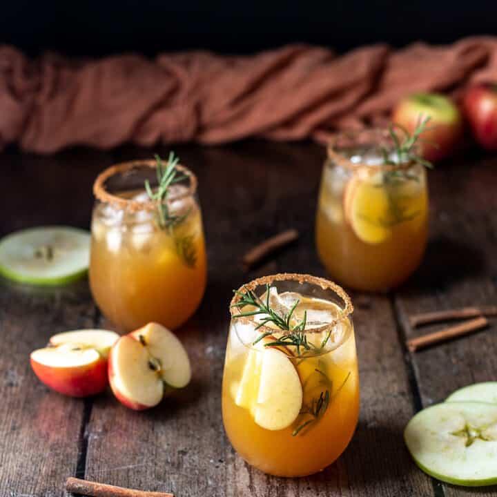 three apple cider margaritas, an orange linen in the background