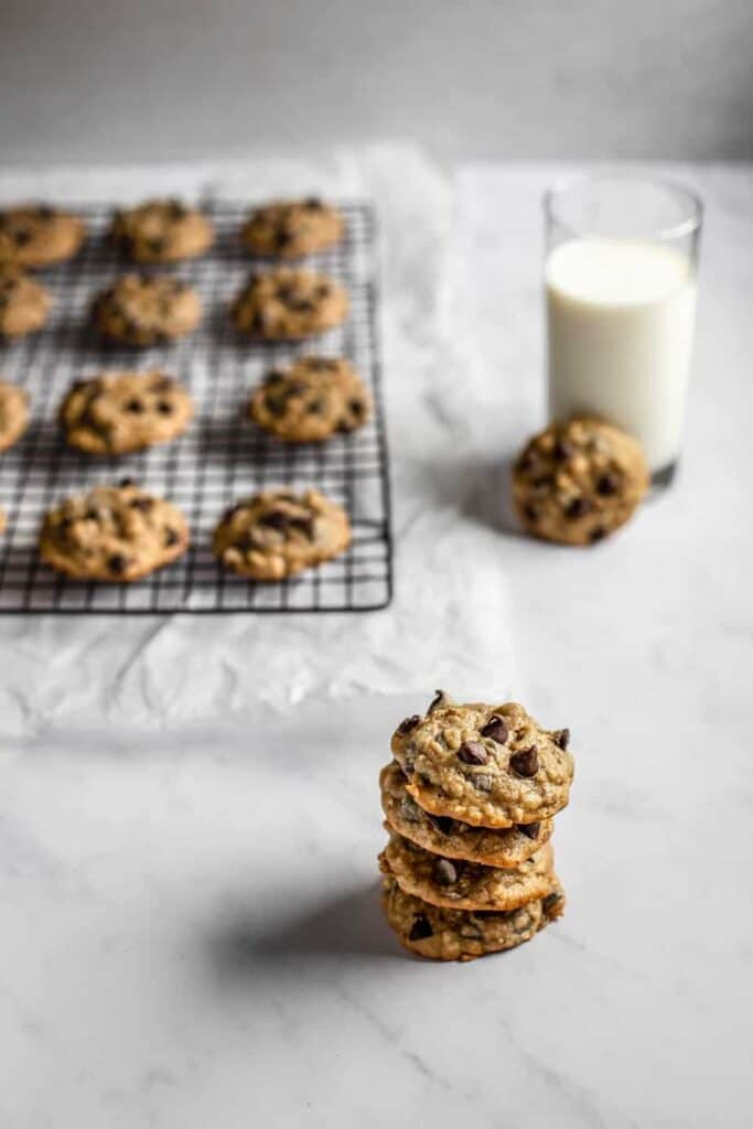 a stack of banana bread cookies in the foreground, with more cookies on a cooling rack and a glass of milk in the background