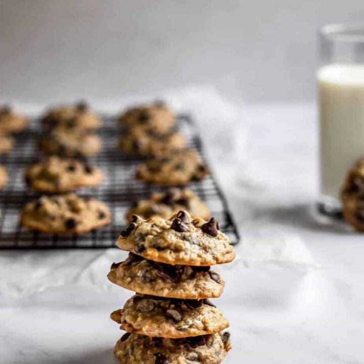 a stack of chocolate chip banana bread cookies, with more cookies on a cooling rack in the background