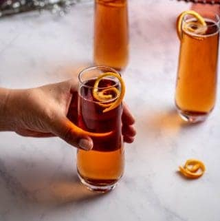 three chambord kir royale cocktails with orange twists; a hand is reaching for one