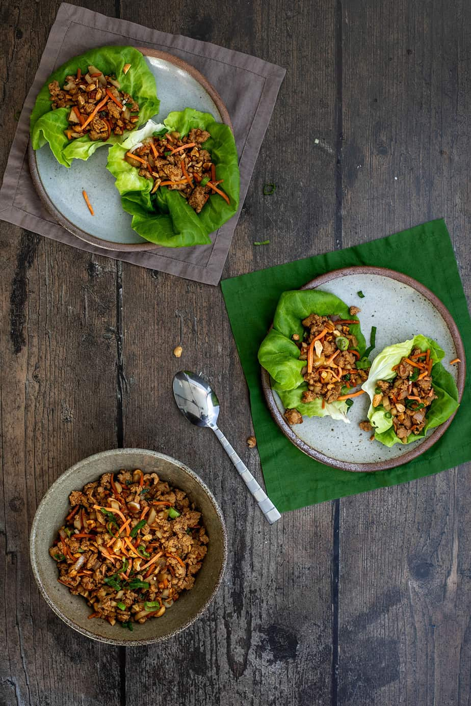 two plates with two pf changs chicken lettuce wraps each, a bowl with lettuce wrap filling