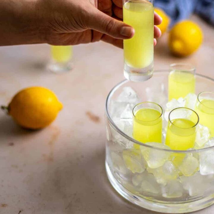 a glass dish with tall sides is filled with ice and has 4 shot glasses filled with limoncello; a hand is reaching in from the left and holds another shot glass with limoncello