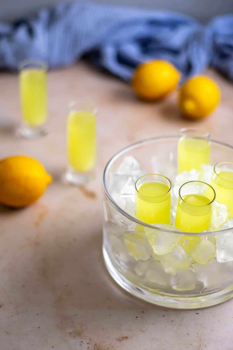 a glass dish is filled with ice and holds 4 tall shot glasses of limoncello; two shot glasses are in the background, along with lemons