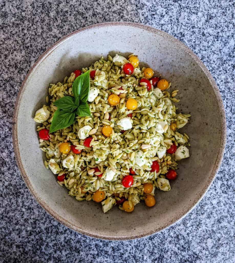caprese orzo pasta salad in a serving bowl on a granite countertop