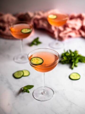 three coupe glasses on a white marble slab, glasses are filled with pink liquid and are garnished with a cucumber slice