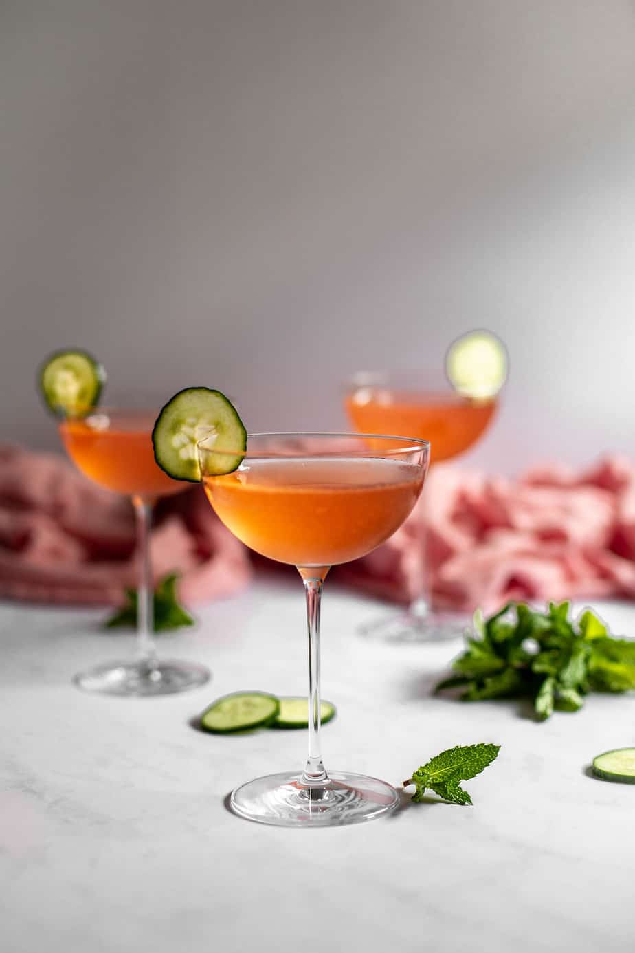 a straight on view of three coupe glasses filled with pink liquid and garnished with cucumber slices