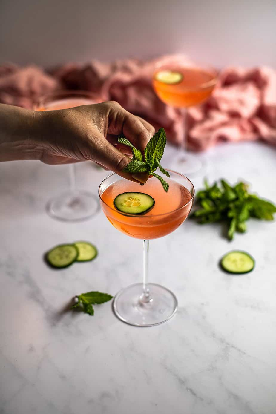 a hand getting ready to place a sprig of fresh mint into a couple glass filled with pink liquid and garnished with a cucumber slice