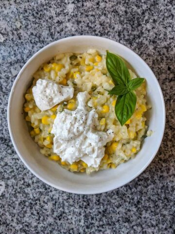 corn and jalapeño risotto, garnished with burrata cheese and fresh basil, in a white bowl on a black and white granite countertop