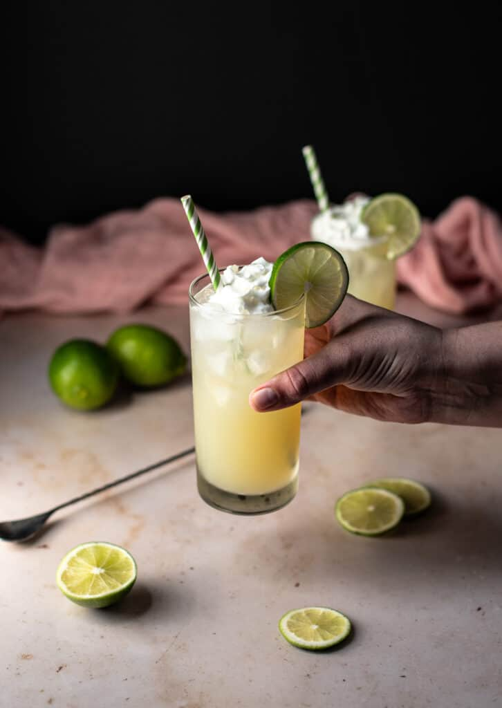 a hand holding a key lime pie crush cocktail