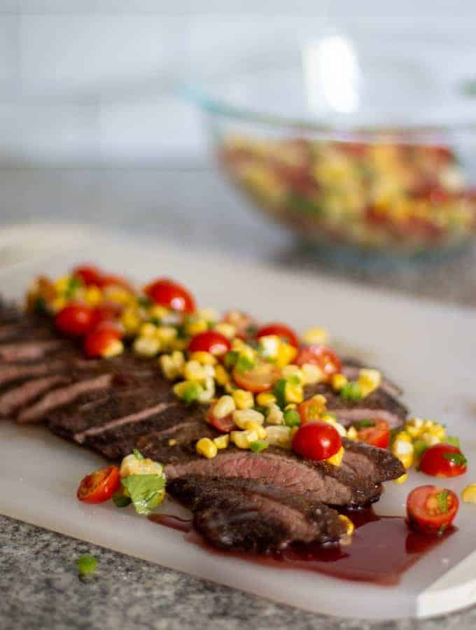 flank steak, sliced, laying on a white cutting board, topped with corn salsa