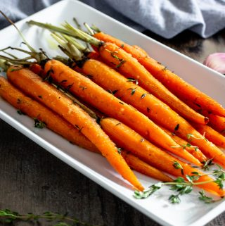 roasted petite carrots with green tops on a white serving dish