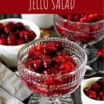 cranberry jello salad in a clear glass cup on a dark wood backdrop