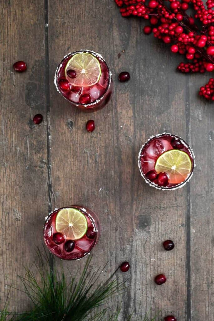 seen from overhead, three glasses of cranberry margaritas are on a wooden backdrop; glasses are garnished with lime slices, fresh cranberries, and salt rims