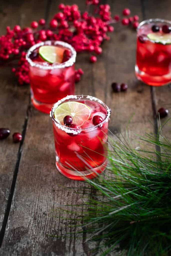 three glasses full of cranberry margaritas with salt rims, lime slices, and fresh cranberries; glasses are on a warm wooden backdrop; frame is decorated with faux red berries and pine bough