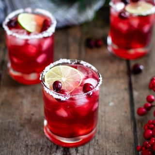 three short glasses filled with red cranberry margaritas; glasses are garnished with a salt rim, a slice of lime, and fresh cranberries; the glasses are sitting on a warm wood backdrop