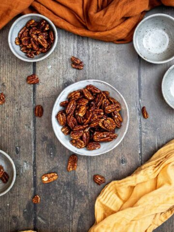 a medium-sized bowl of candied pecans in the center, 1 smaller bowl of nuts above and to the left, and 1 small empty bowl, on a dark wooden background