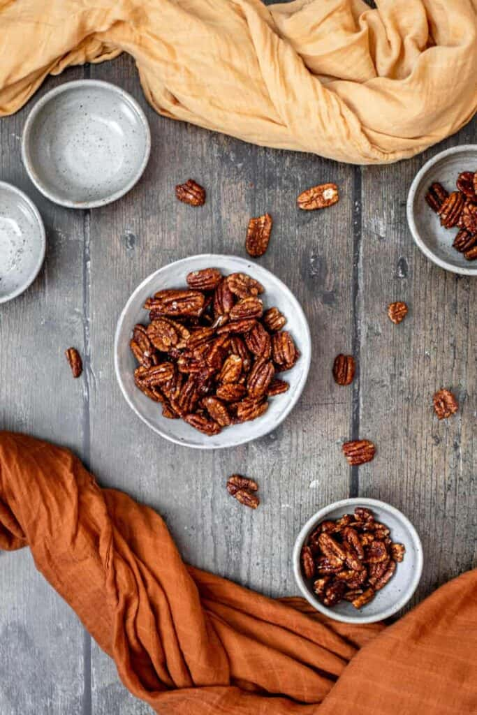 a medium-sized bowl of candied pecans in the middle, flanked by 2 small bowls of nuts on the right and 2 small empty bowls on the left, on a dark wood backdrop