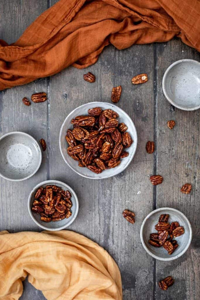 candied pecans in 3 small bowls, with 2 small empty bowls on either side, sienna and light yellow linens for accents, on a rich, dark wood background
