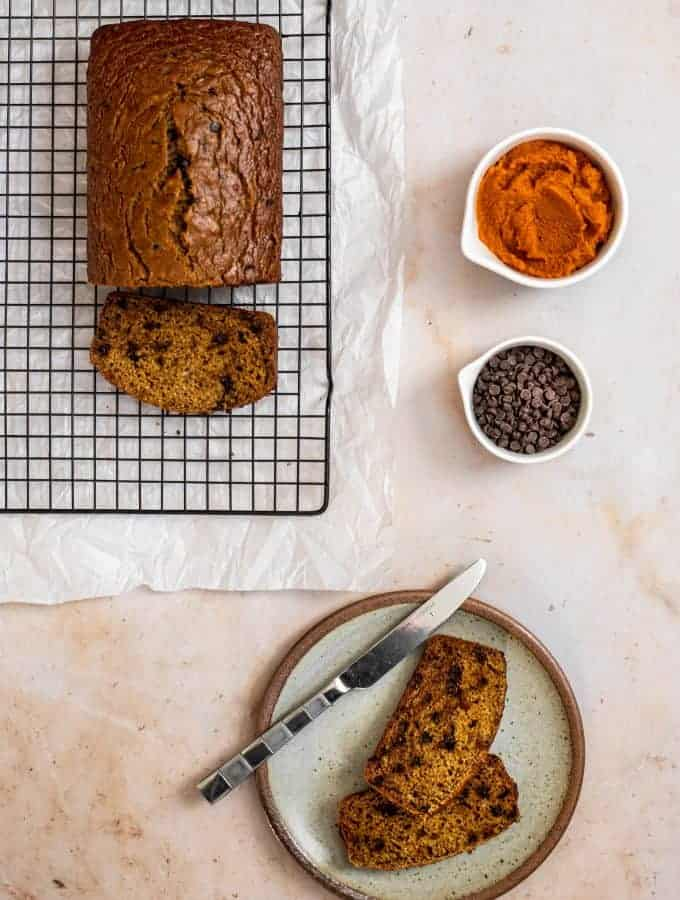 viewed from above, a loaf of pumpkin banana bread on a wire baking rack with one cut slice on the rack, two slices on a plate with a knife, and pumpkin puree and chocolate chips in small bowls set off to the side