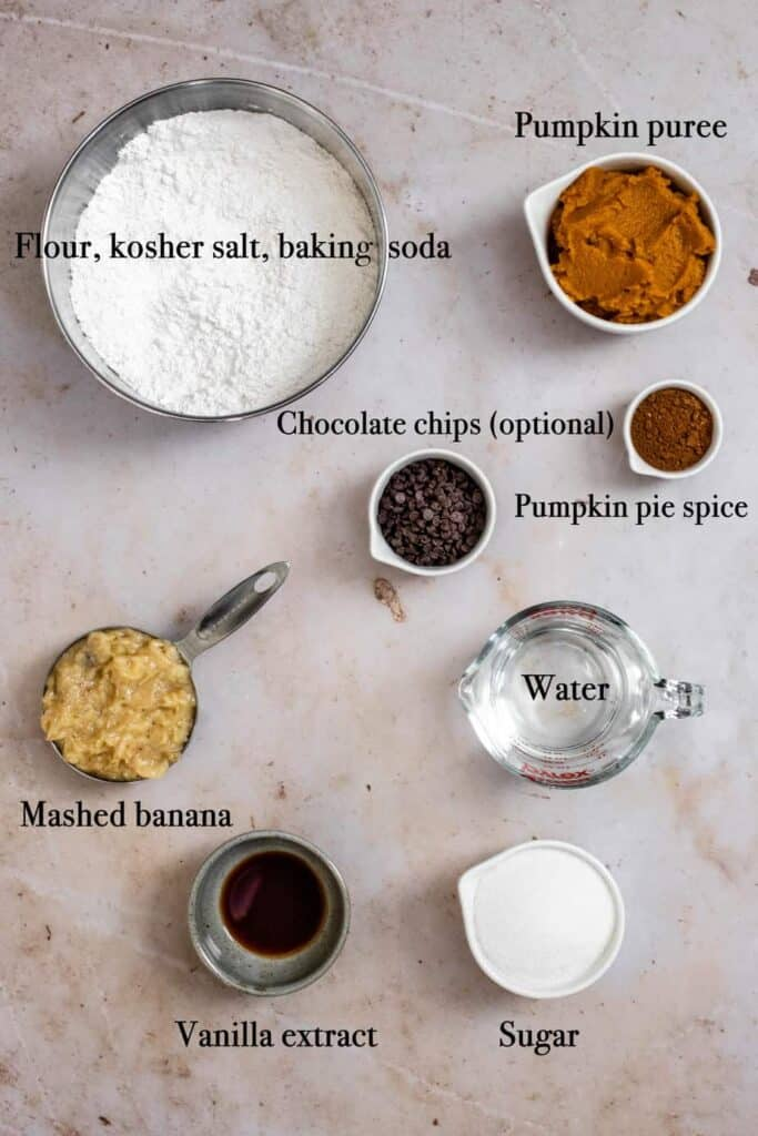 ingredients used to make pumpkin banana bread, photographed from above, labeled with black text, and set on a warm-colored background