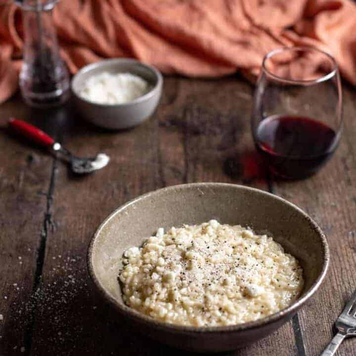 bowl of cacio e pepe risotto with glass of wine, dish of cheese, and pepper mill in background