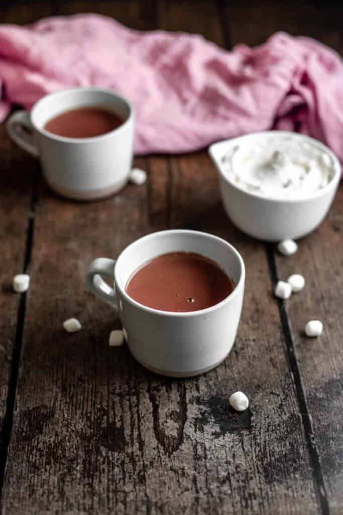 two mugs of red wine hot chocolate, one bowl of whipped cream