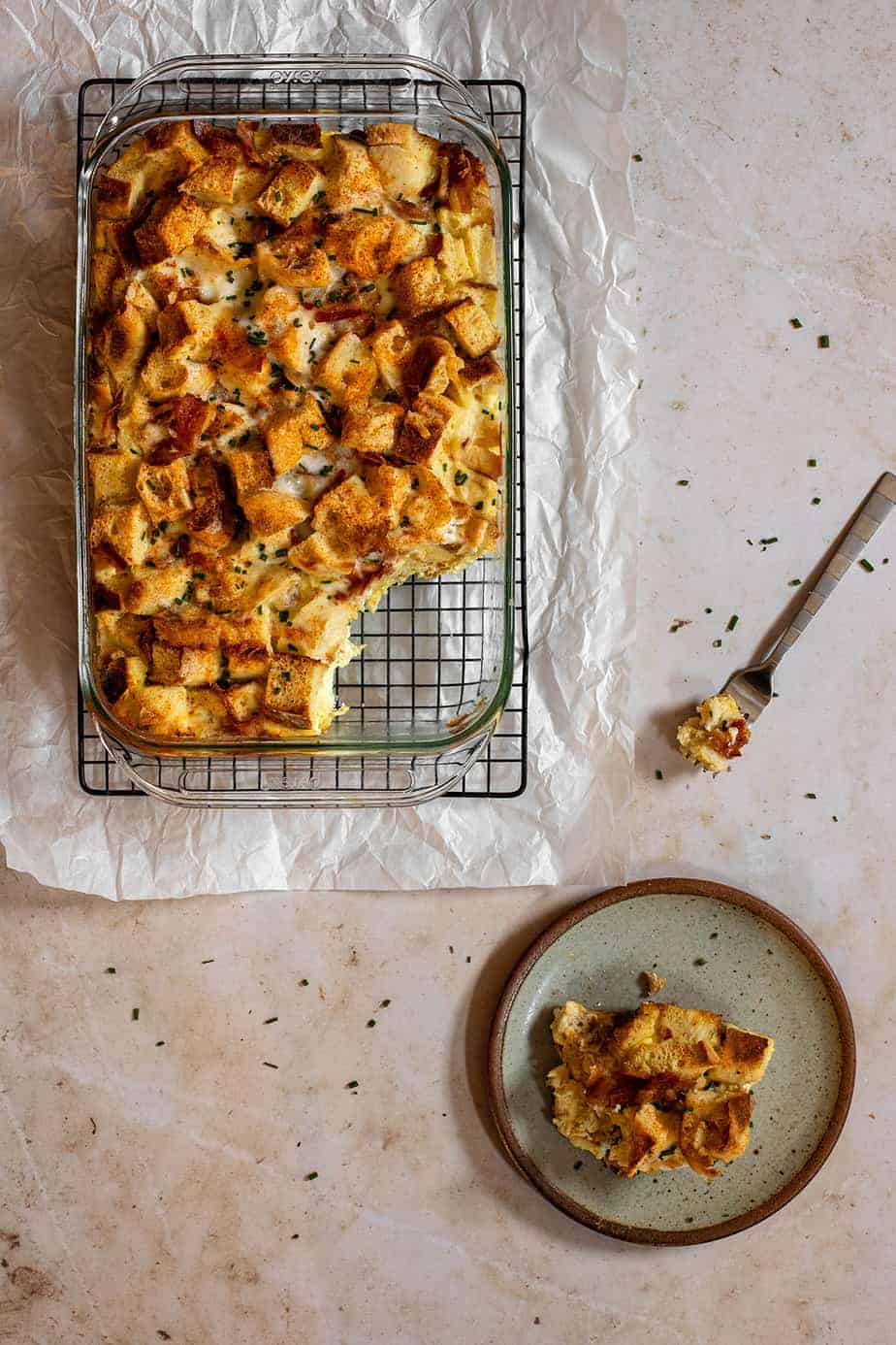a 9x13-inch pan full of english muffin breakfast casserole with a scoop taken out of it