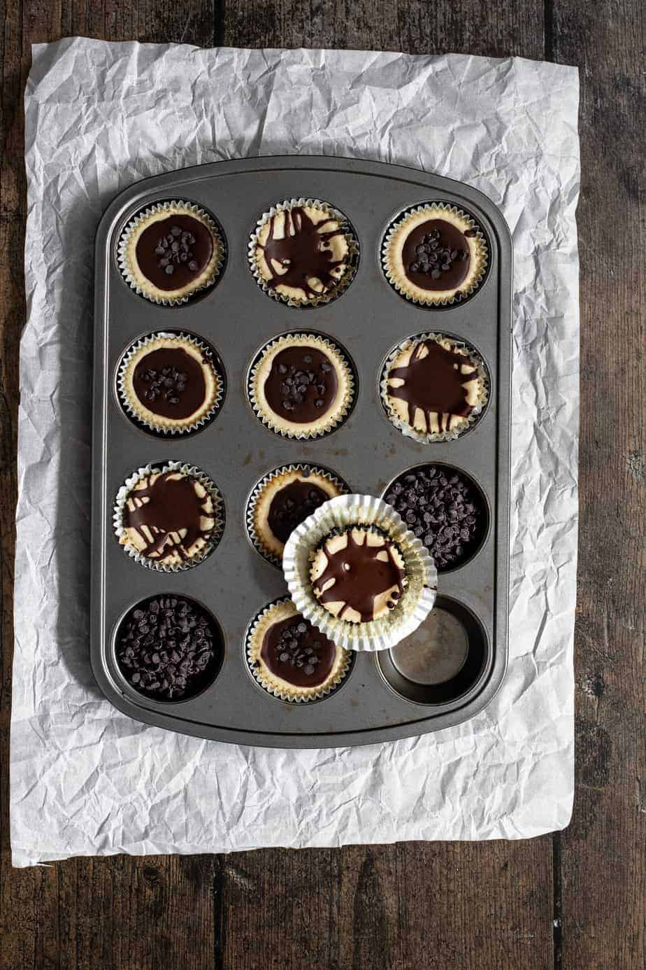 an overhead shot of a muffin tin that's full of mini cheesecakes