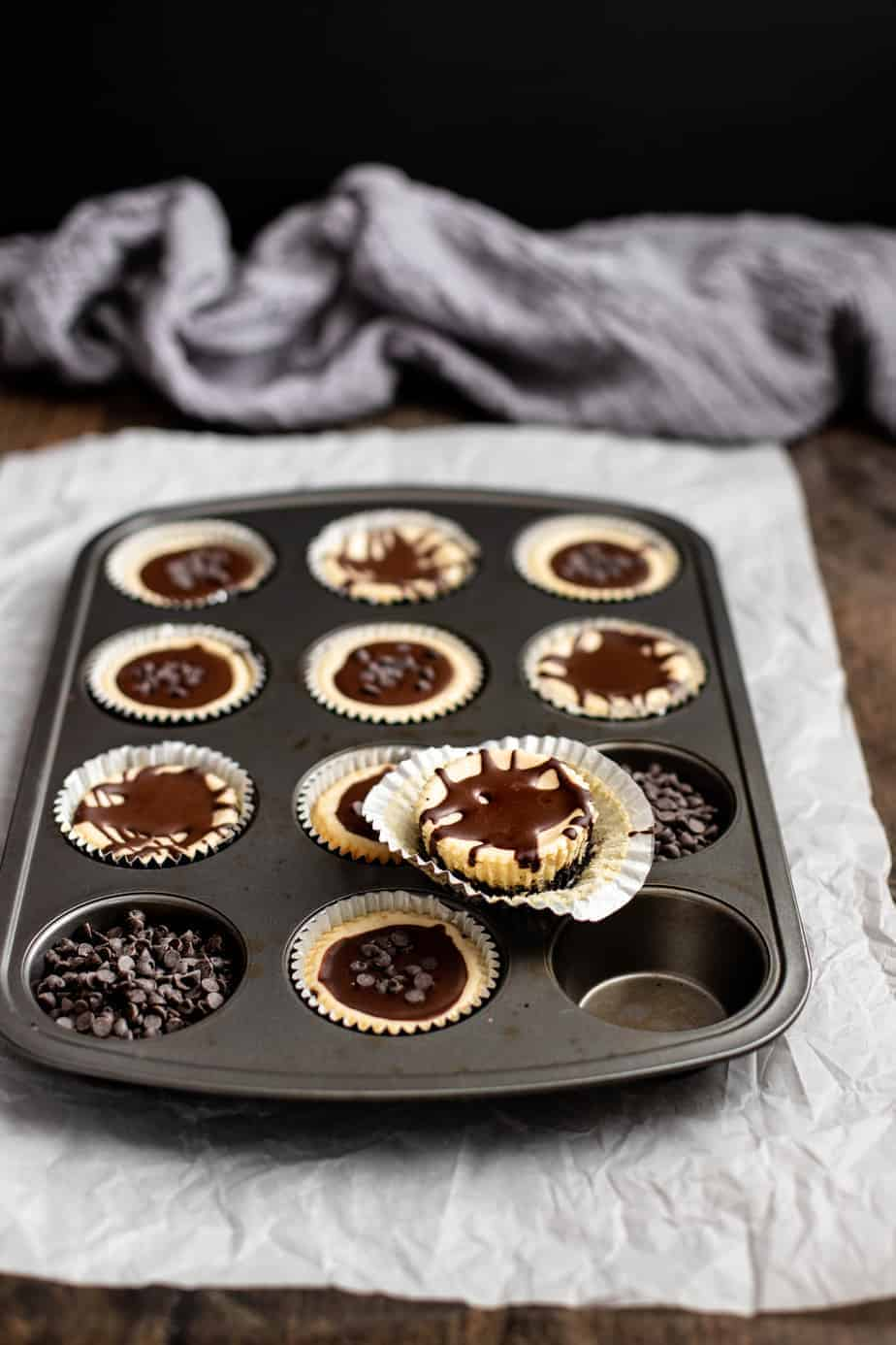 a muffin tin is full of mini cheesecakes