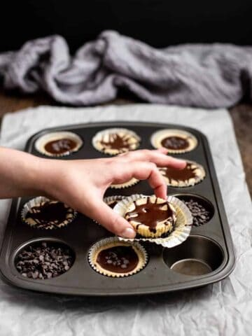 a muffin tin with mini cheesecakes, a hand is reaching for one