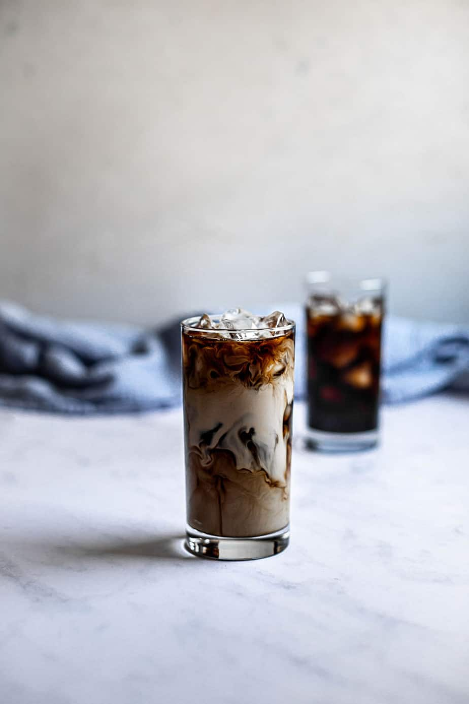 two glasses of iced coffee, one with cream
