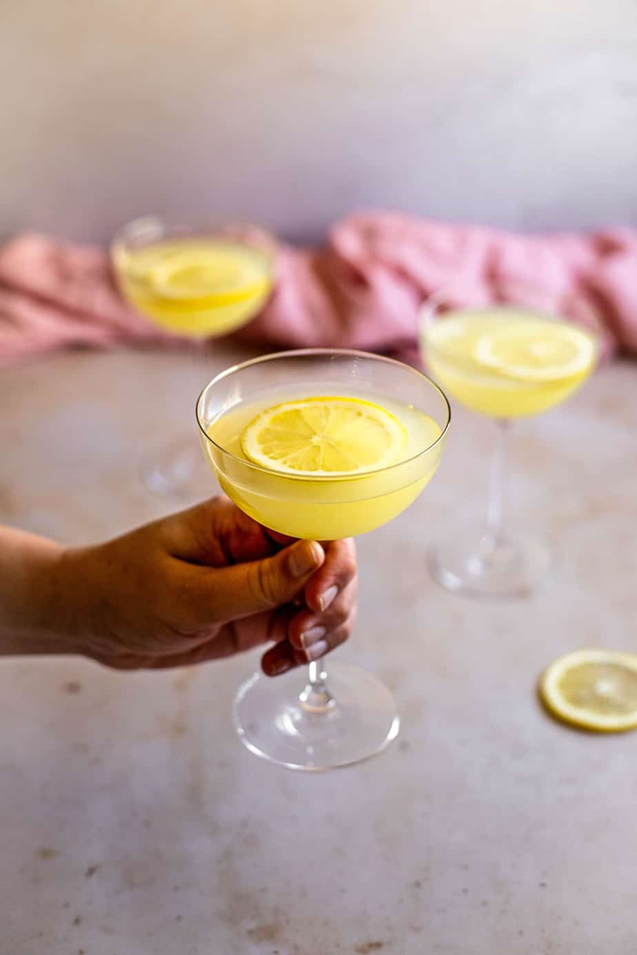 a hand holding a coupe glass with a limoncello martini in it