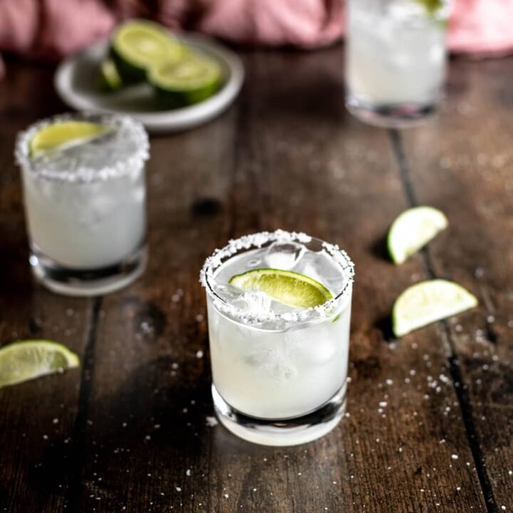 three margaritas on a dark wooden background, a dish of lime wedges in the left rear