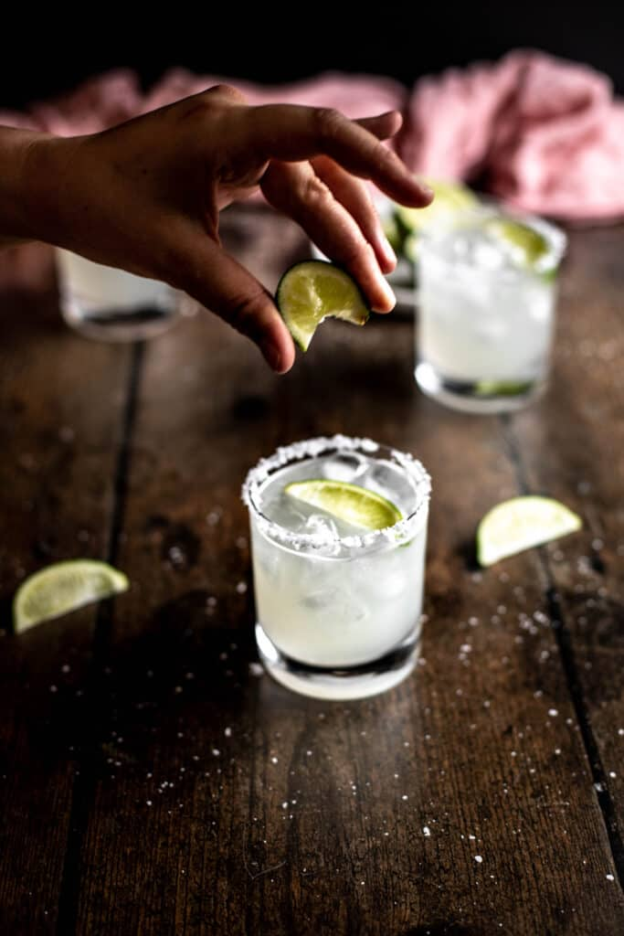 hand squeezing a lime wedge into a margarita
