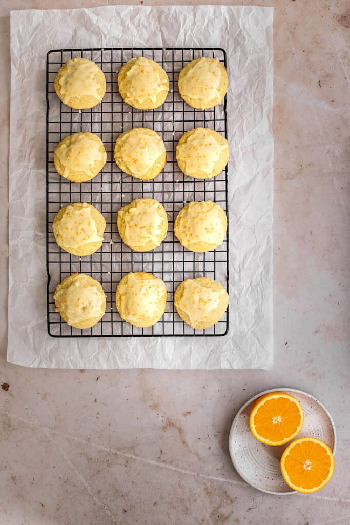 an overhead view of 12 orange cookies on a wire cooling rack, a dish with halved oranges in the lower righthand corner