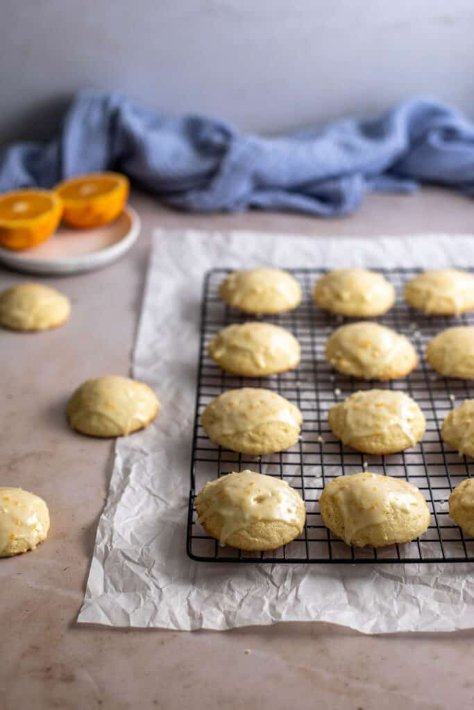 45 degree angle view of orange cookies on a wire cooling rack, 3 cookies to the left not on the rack, halved oranges in background