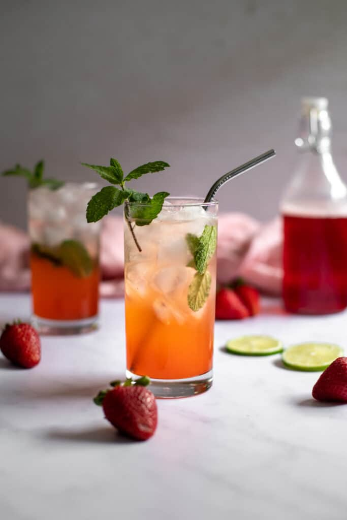 a head on photo of two strawberry mojitos, a bottle with red strawberry simple syrup in the background