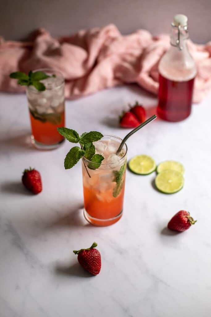 a 45 degree angle photo of two strawberry mojitos, a bottle with red strawberry simple syrup in the background