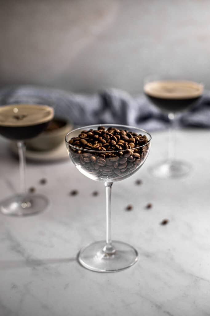 a coupe glass filled with coffee beans in the foreground, two coupe glasses filled with espresso martinis in the background
