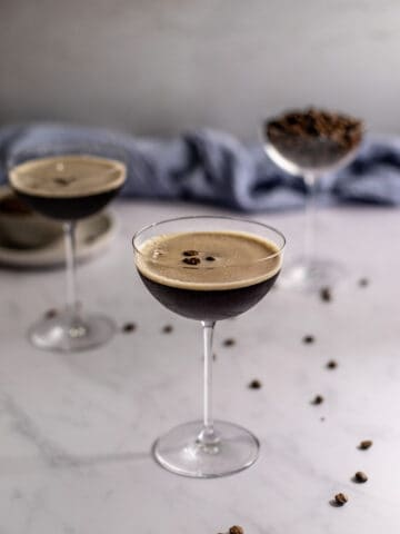 two espresso martinis in coupe glasses, one coupe glass filled with coffee beans