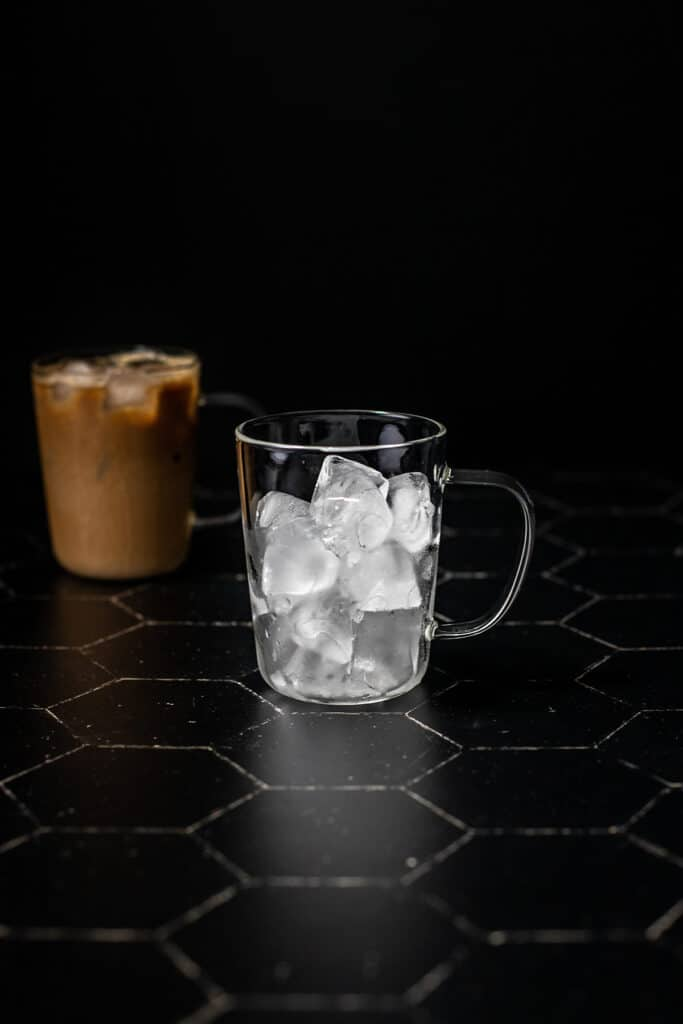 a clear glass mug filled with ice on a black background