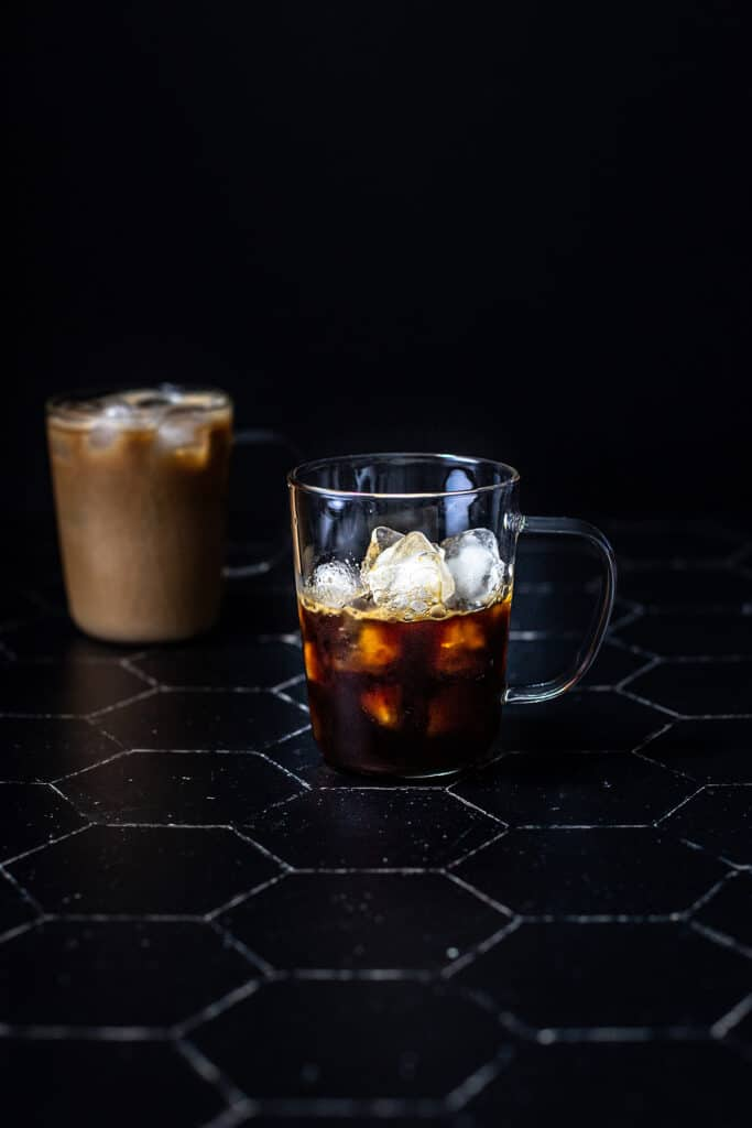 a clear glass mug filled with ice and espresso