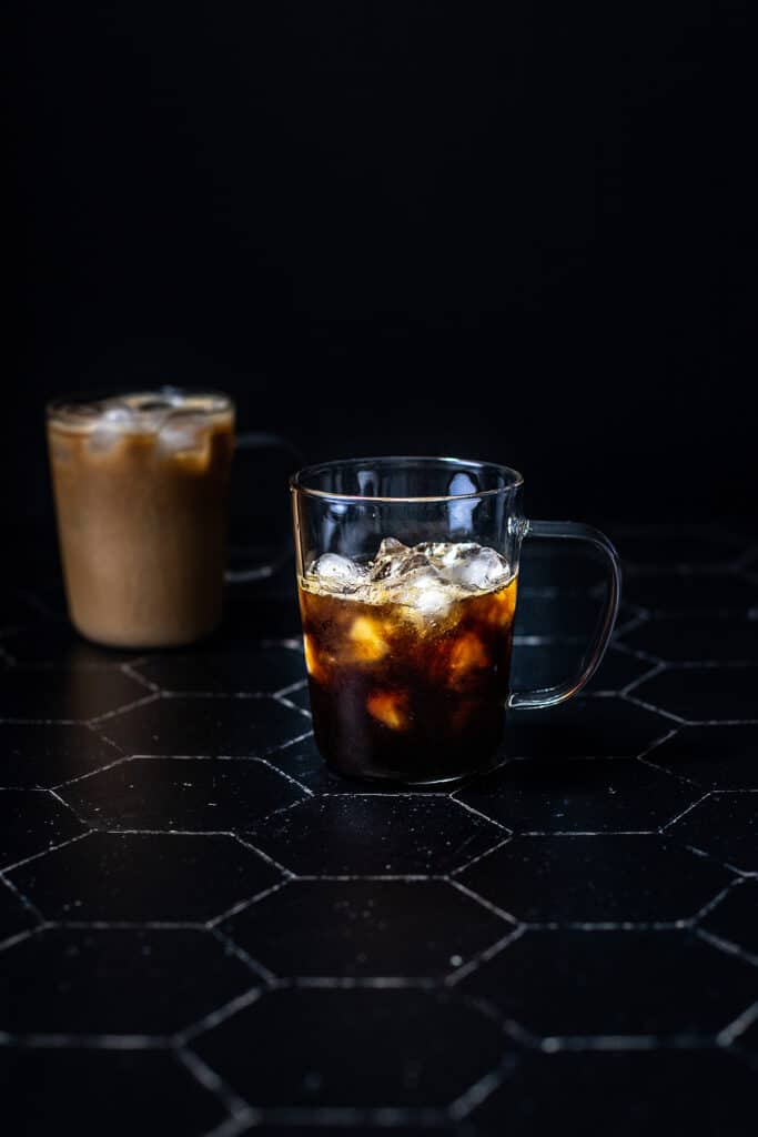 a clear glass mug filled with ice, espresso, and caramel syrup