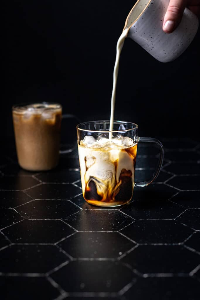 a clear glass mug filled with ice, espresso, and having milk poured into it