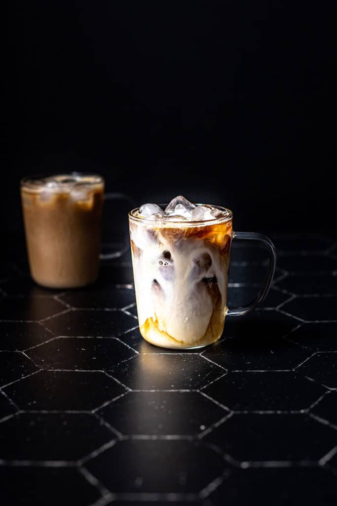 a clear glass mug filled with espresso and ice, milky swirls