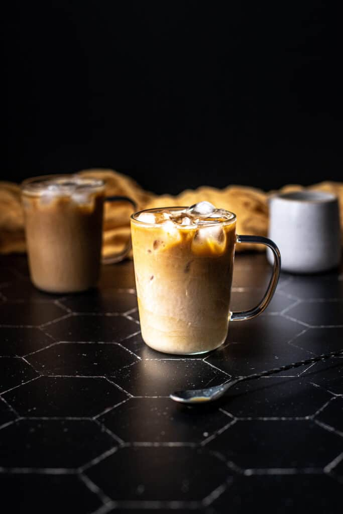 a clear glass mug filled with an iced latte