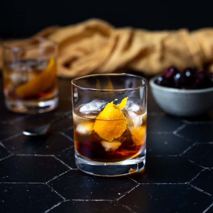 a maple old fashioned on a black tile background
