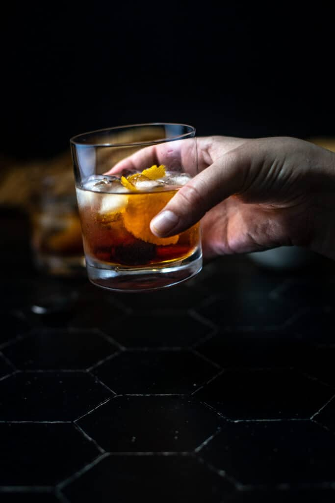 a hand holding a maple old fashioned